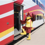 Large red roadrunner mascot standing by a train
