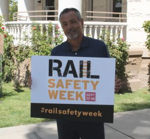 Robert Gonzales holding a Rail Safety Week Poster