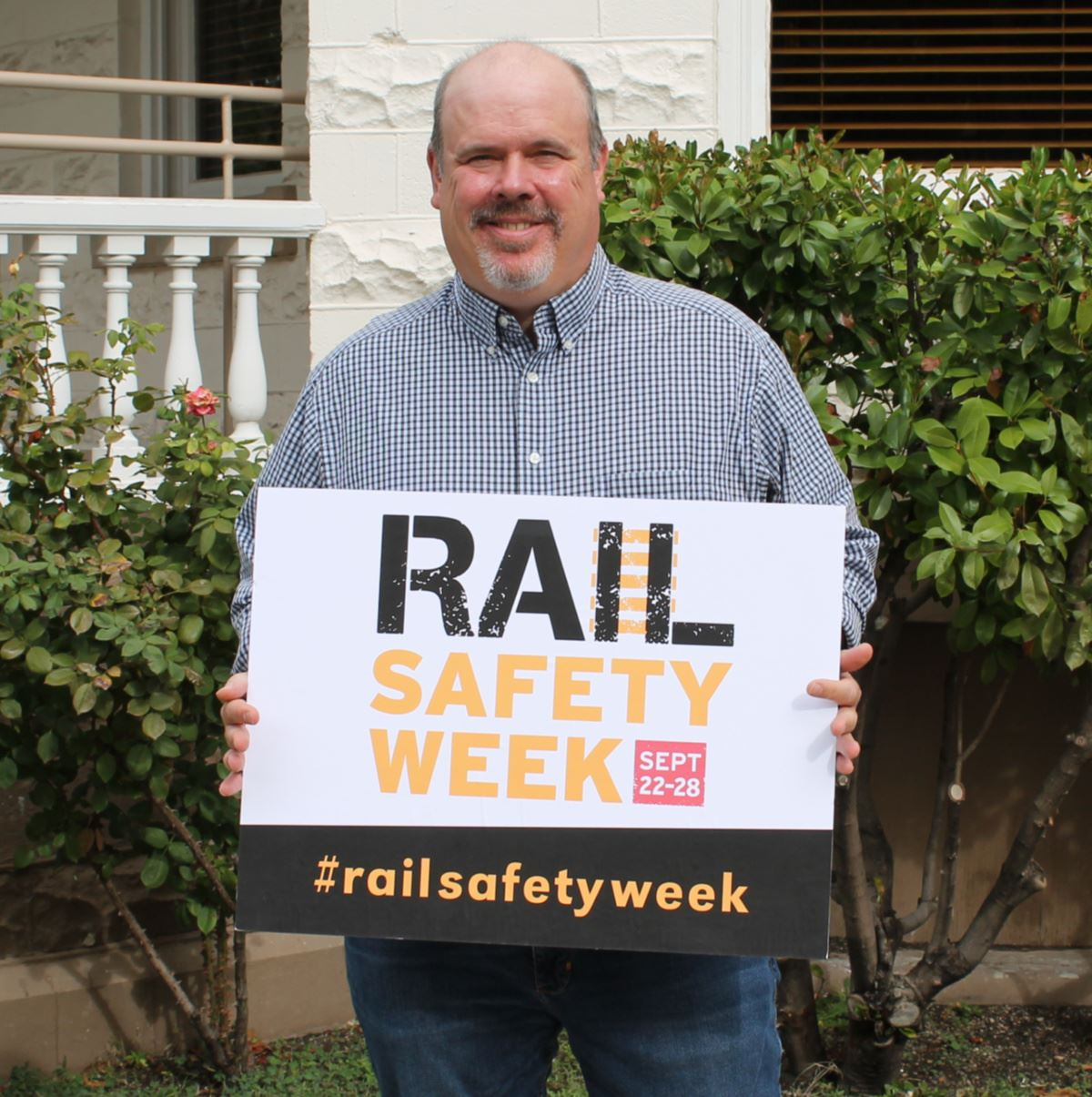 Terry Doyle holding a Rail Safety Week sign