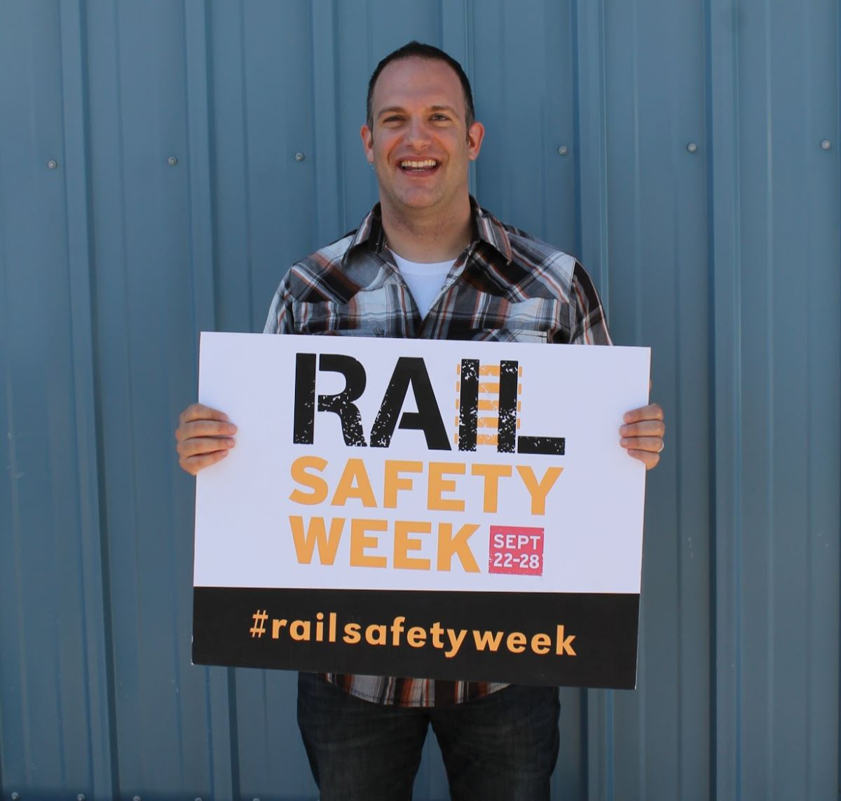 James Breiterman holding rail safety sign