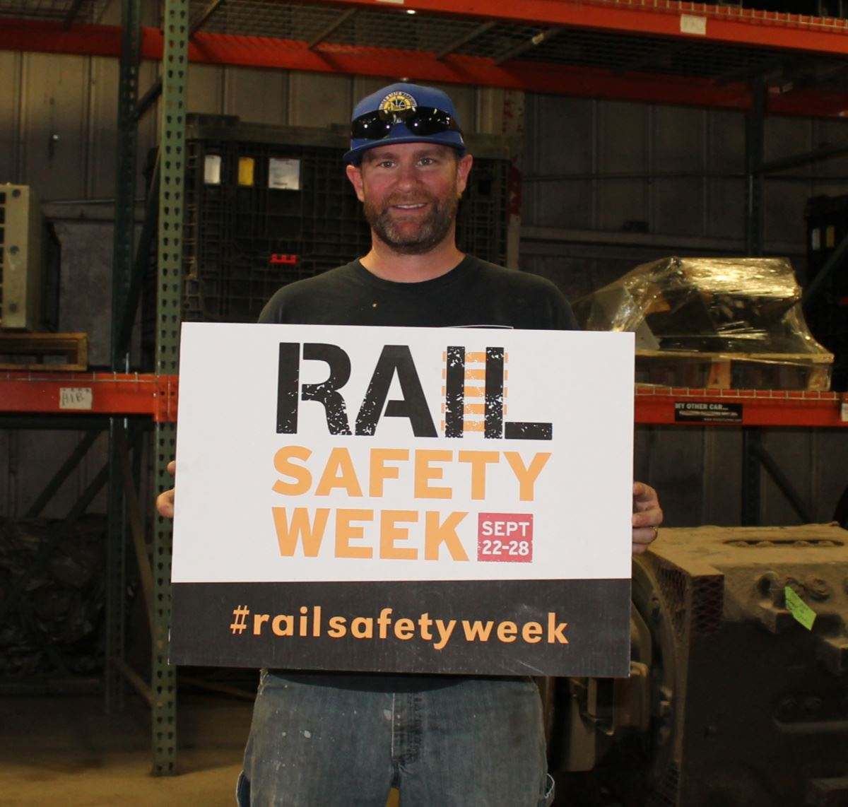 Josh Brennan holding rail safety sign