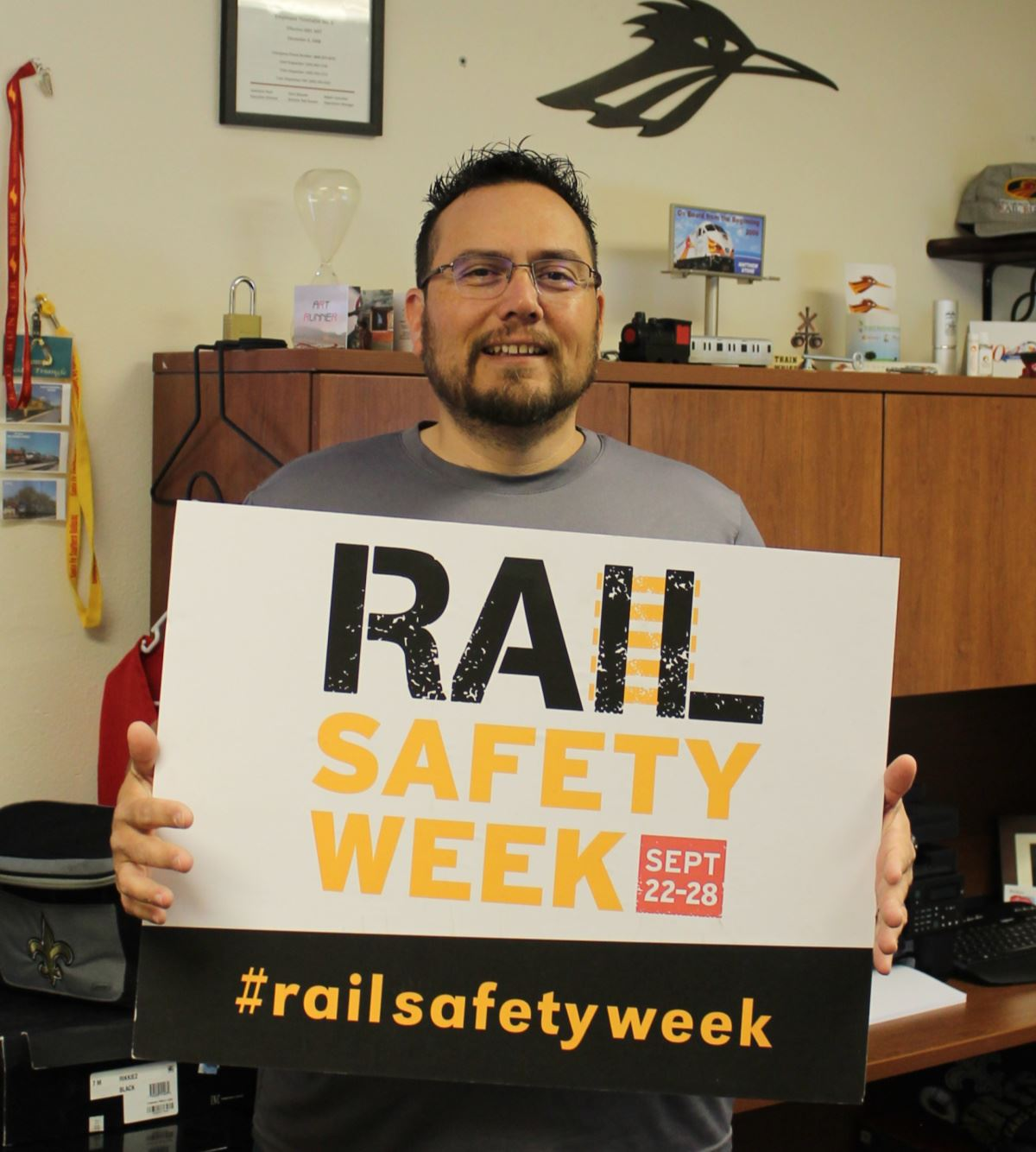 Matt Stone holding rail safety sign